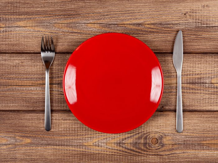 Extreme weight loss, a red plate on a table with a fork and knife