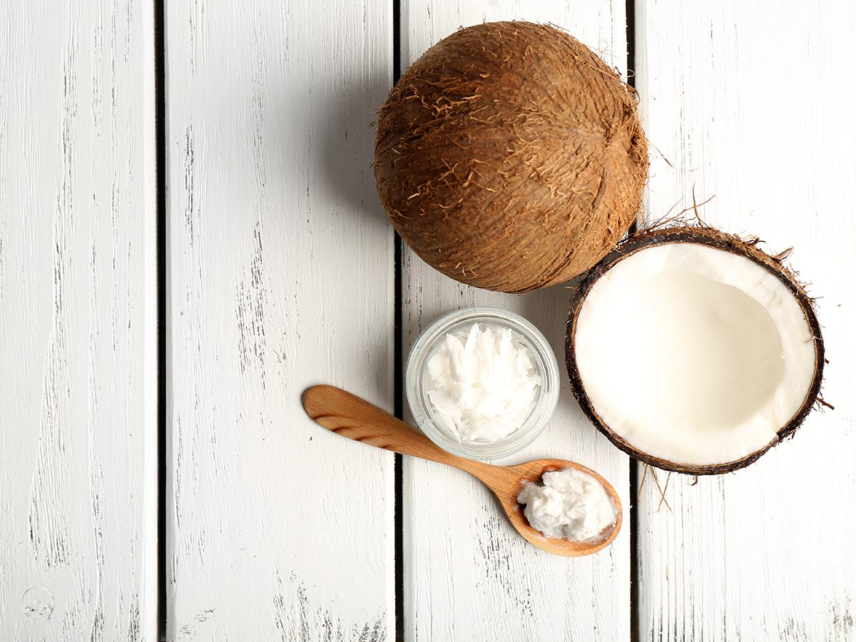 Healthy foods, a tub and spoonful of coconut oil next to a halved coconut