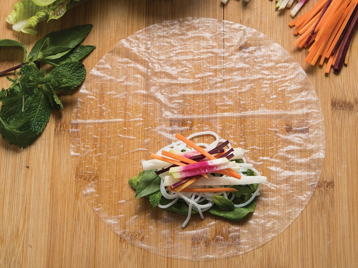 Setting down ingredients into rice paper rolls