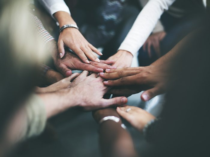 Self love, people stand in a circle and put all of their hands together in the middle