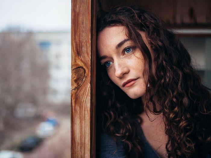 Self love, sad woman looks out window