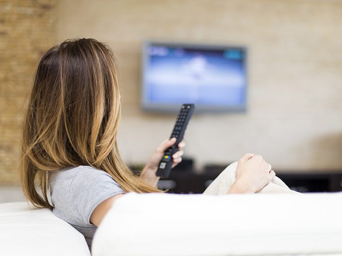 Self love, woman holds up remote control as she watches TV on the couch