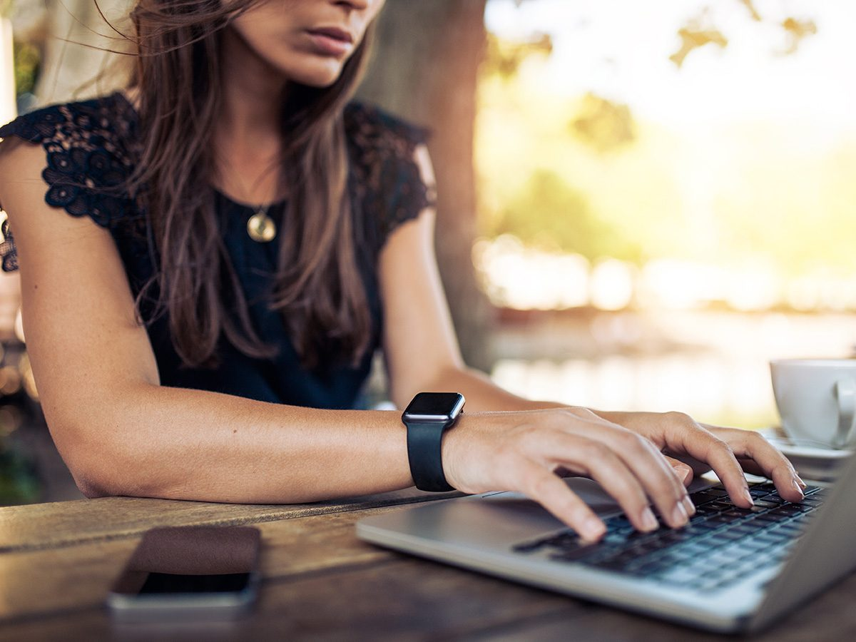 Self love, woman types on laptop computer from an outdoor picnic bench