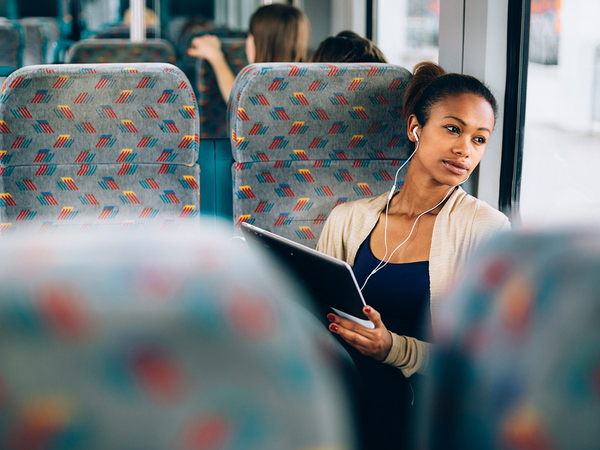 Self love, woman creates a mantra on the bus as she sits listening to music