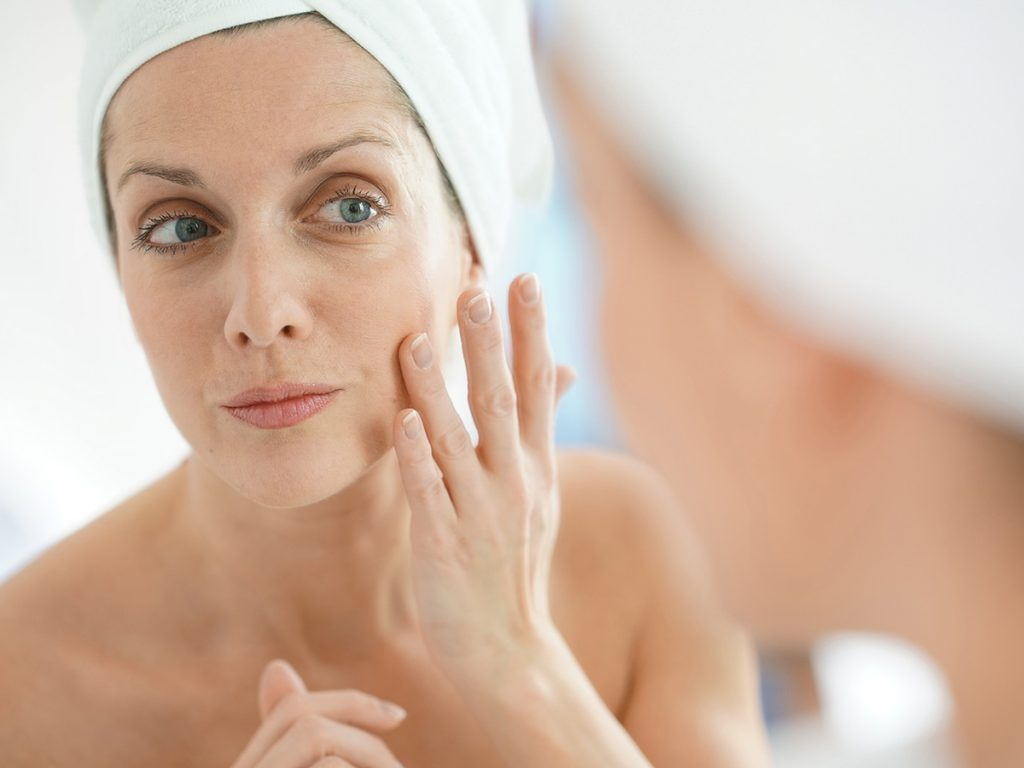 Skin care routine, Mature woman applies face cream in the bathroom