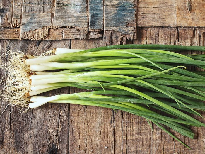 Superfoods, green onions on a wooden table