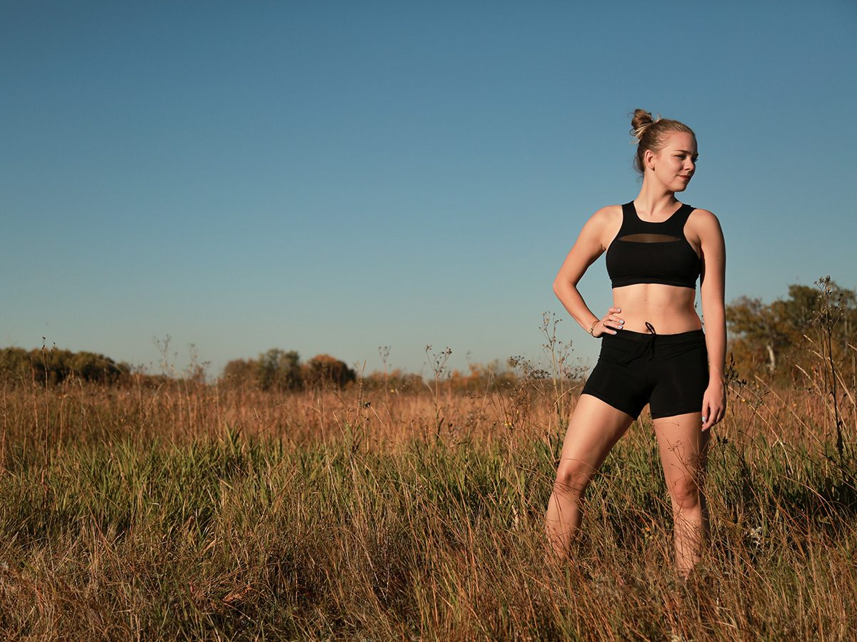 Workout gear, Woman standing in a field wearing black Lunapads sport shorts