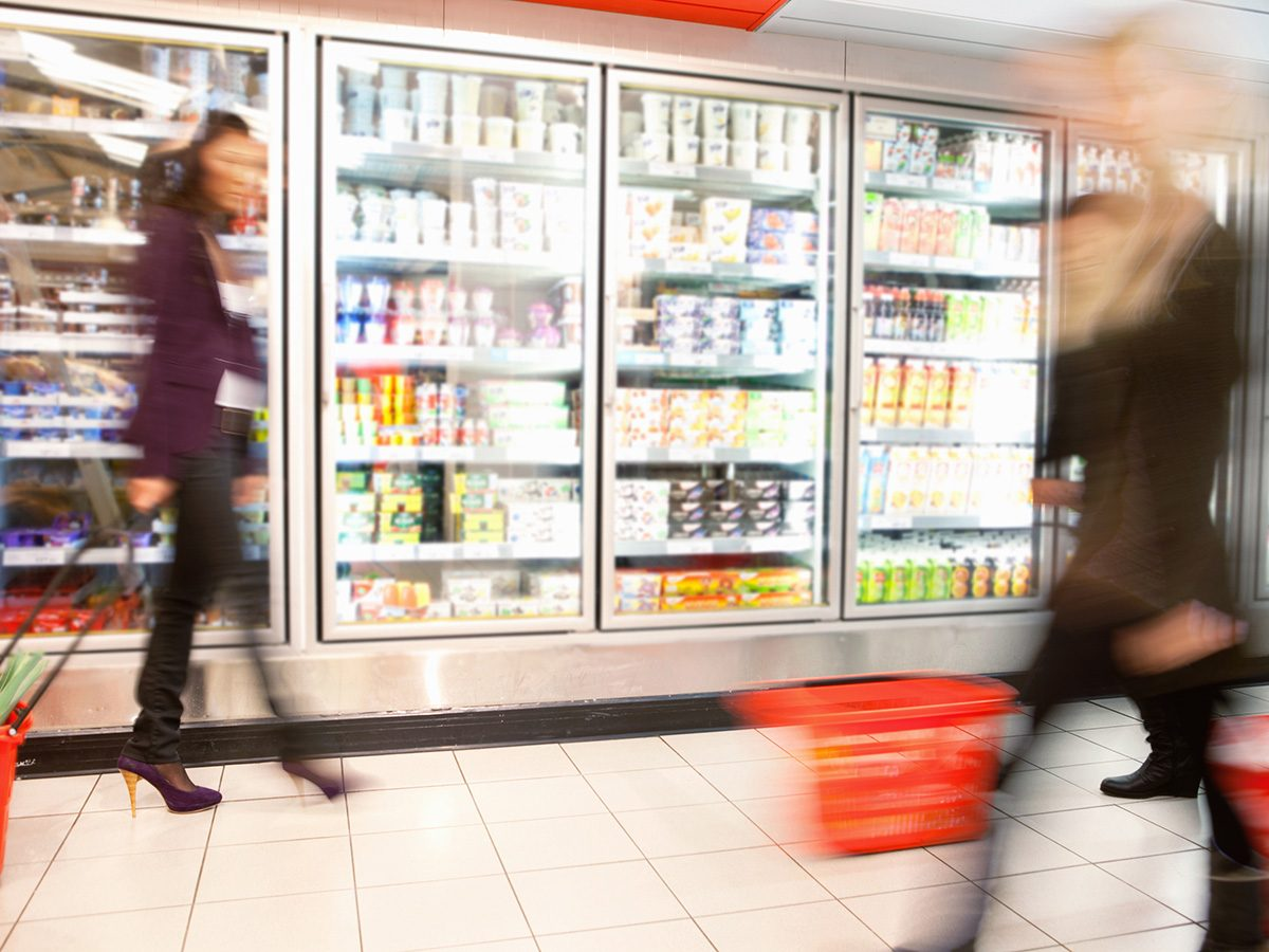 Zero calorie foods, blurry women walking throug the frozen foods aisle at a grocery store