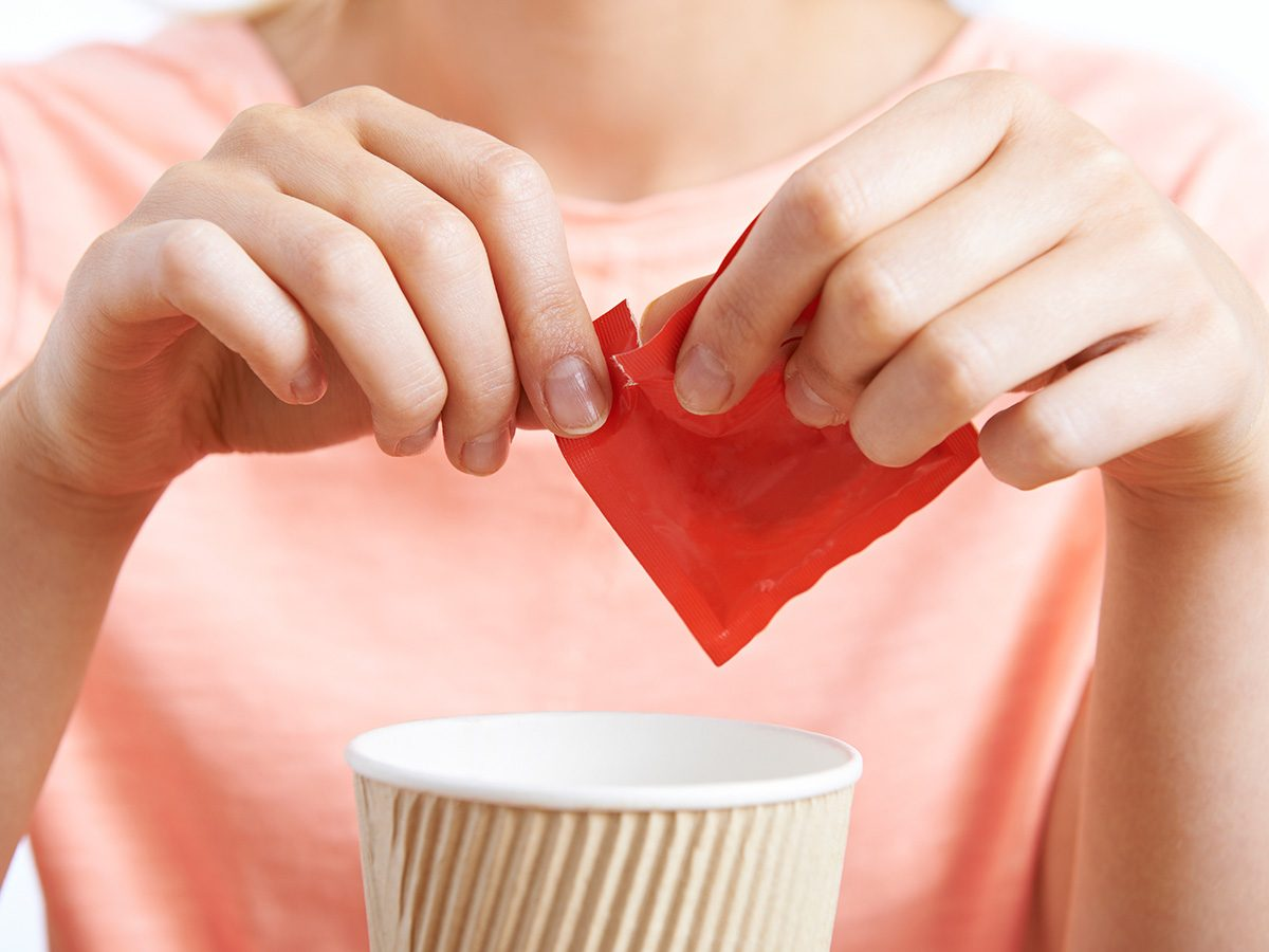 Zero calorie foods, woman adding pack of splenda to her coffee