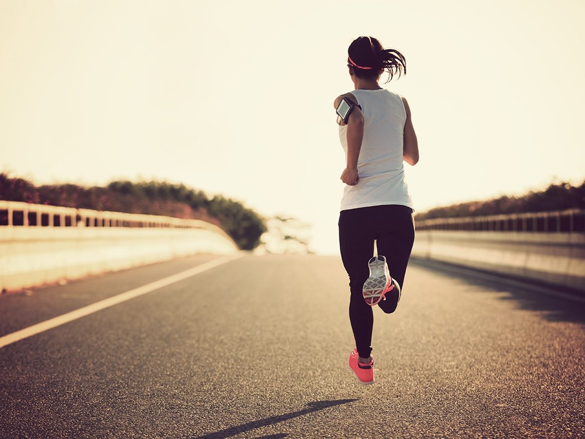 Run club, woman runs on an open road