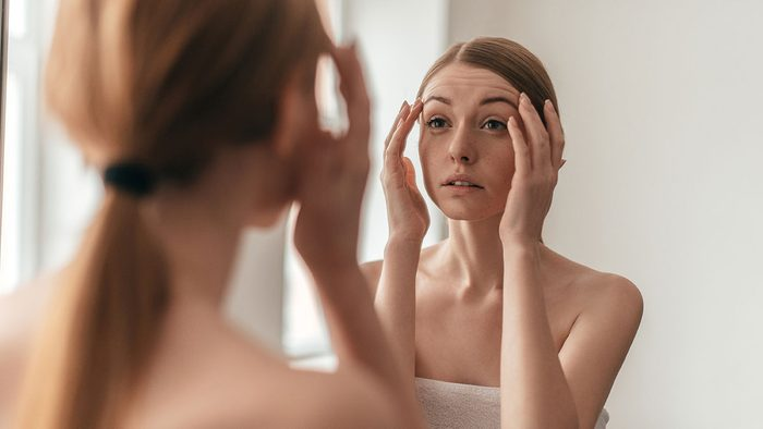 Breast Cancer Advancements, woman looking at herself in the mirror