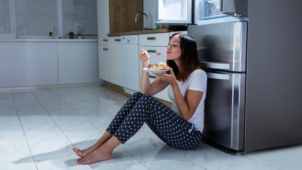 How Sugar Affects Sleep, woman sitting on floor eating