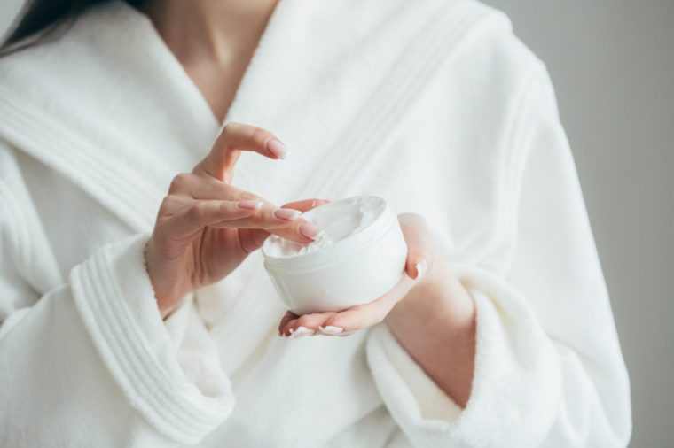 Beautiful groomed woman's hands holding a cream jar on the fluffy blanket. Moisturizing cream for clean and soft skin in winter time. Manicure beauty salon. Healthcare concept. Spa