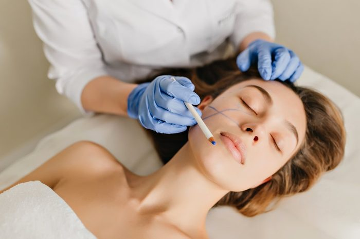 Portrait woman with brunette hair at preparation to rejuvenation, cosmetology operation in beauty salon. Hands in blue gloves drawing on face, botox, beauty