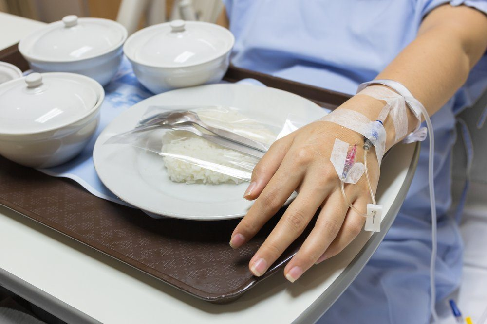 Asian Pregnant Woman patient is on drip receiving a saline solution with cooked rice and other food in white bowl , selective focus.