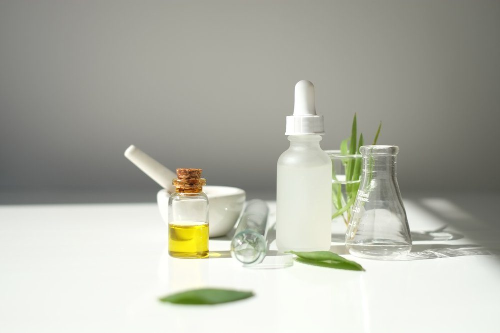 blank cosmetic white serum dropper bottle containers with herbal ingredient and laboratory glass ware. package for branding .Natural organic beauty skincare product concept. alternative medicine.