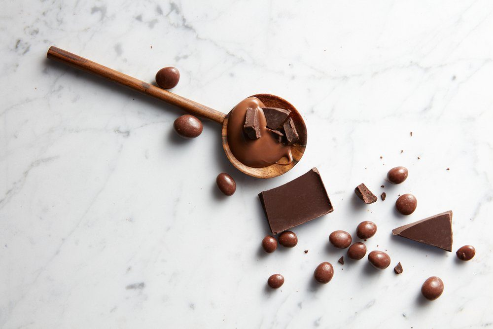 wooden spoon with caramel, chocolate chips and chocolate balls on white marble background
