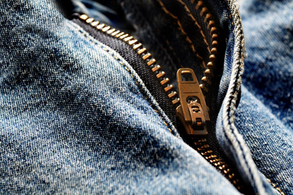 Detail of denim zipper on old worn jeans