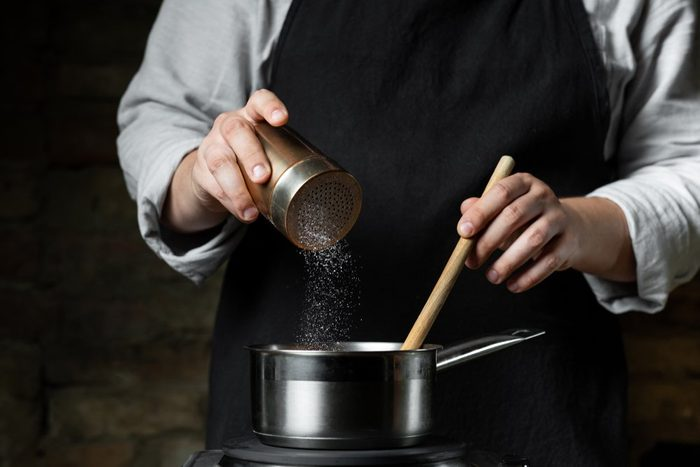 Cooking food in metal saucepan, adding salt by chef hands. Food concept background.