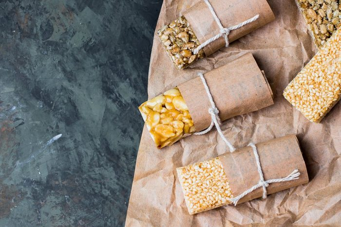 Nuts in caramel, honey on dark table background. Snack food. Unhealthy eating. Copy space