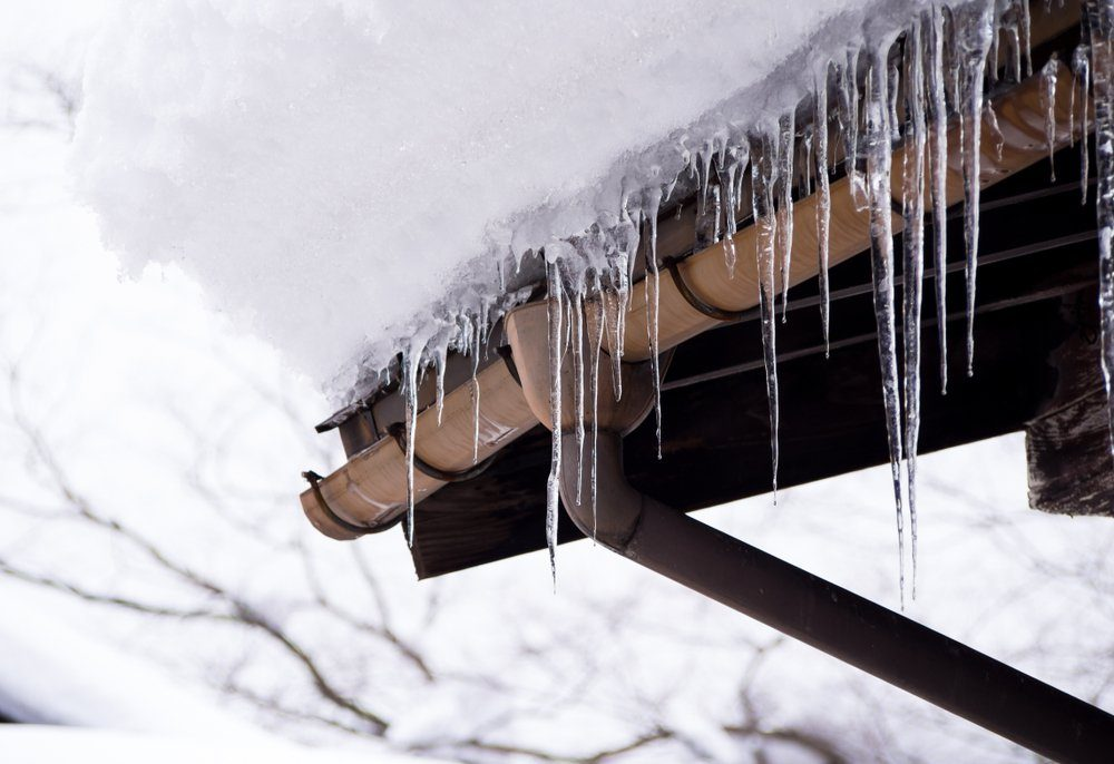 Sharp icicles and melted snow hanging from eaves of roof, Beautiful icicles slowly gliding of a roof.