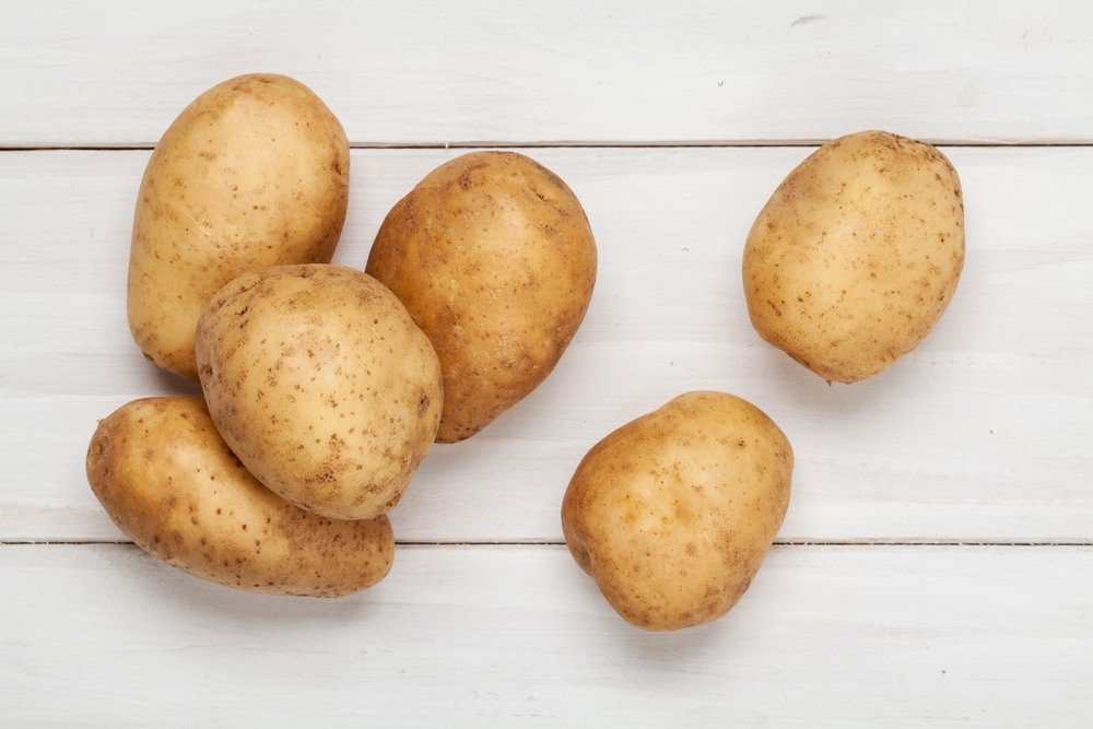 Raw potato on wooden background. Top view.