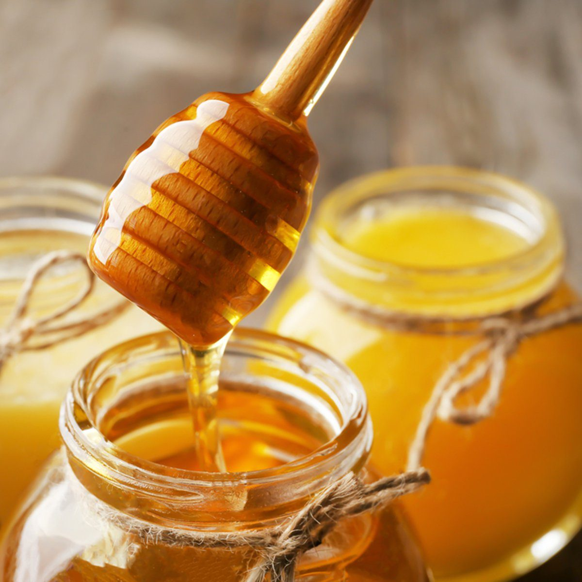 Pouring aromatic honey into jar, closeup
