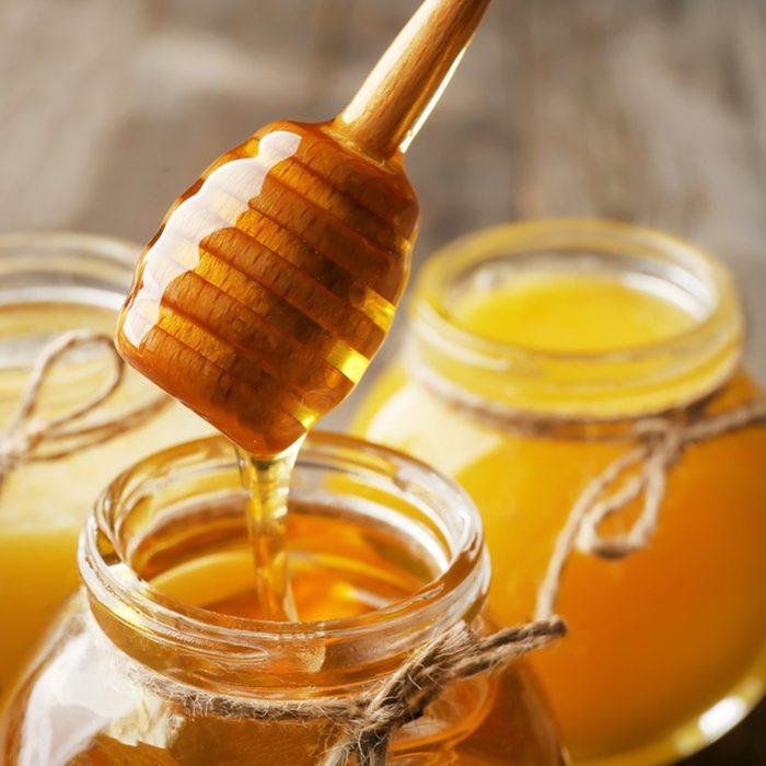Pouring aromatic honey into jar, closeup