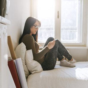A Young Girl Using A Smartphone In The Bedroom