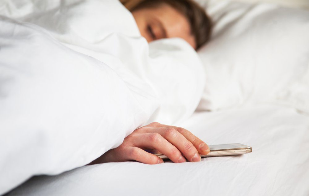 woman sleeping in bed being woken by mobile phone