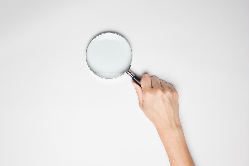 A female hand holds a magnifier at the studio on white background