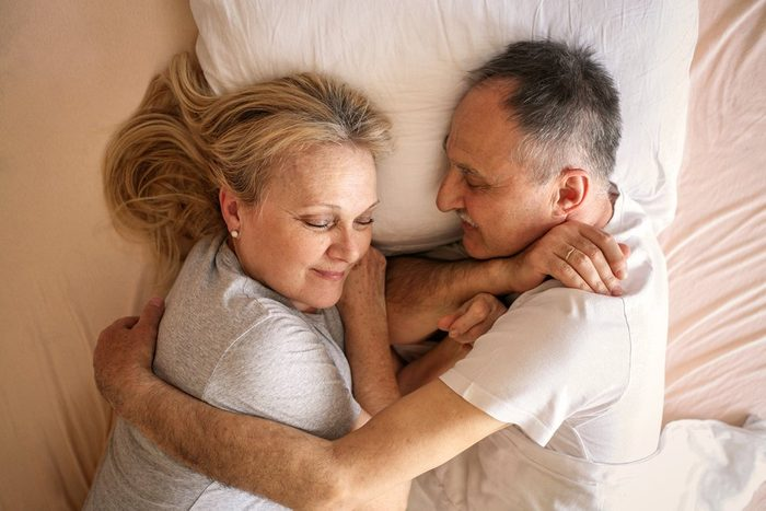 Senior couple sleeping together in bed. Senior couple sleep together on one pillow.