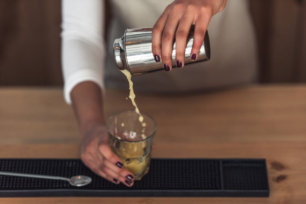 Cropped image of beautiful Afro American barista in apron preparing a cocktail in shaker while standing at bar counter