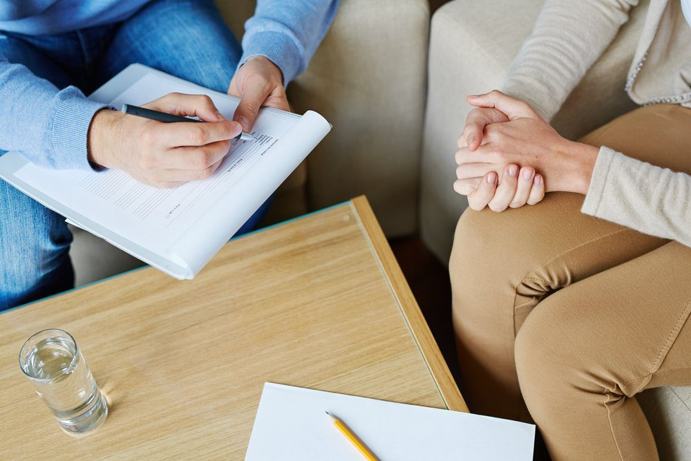 Female patient sitting on armchair and holding her hands together while male psychologist filling in medical card, close-up shot
