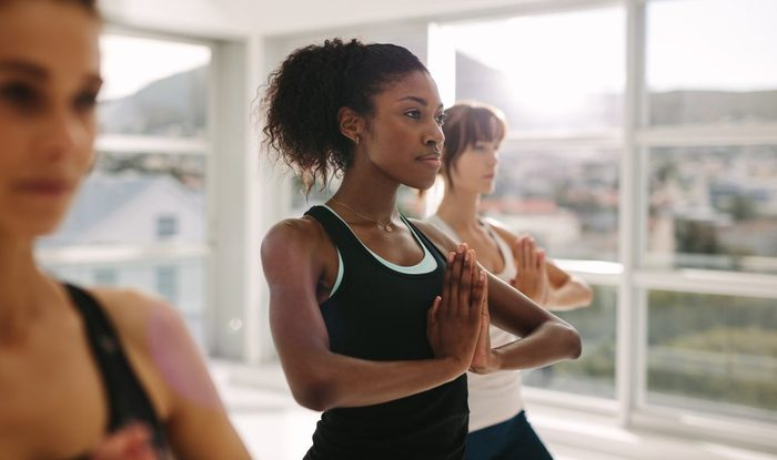 Women stretching and practices yoga in class. Healthy female doing yoga workout in fitness studio. Standing with hands joined.