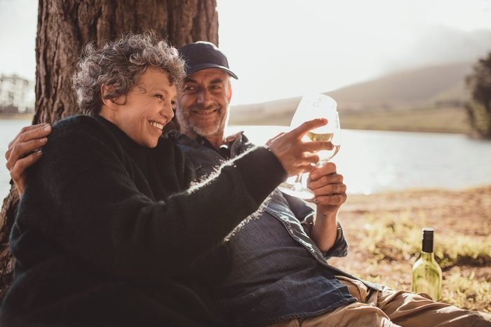 Portrait of happy senior couple sitting near a lake toasting with wine on camping. Woman and man drinking wine at campsite.