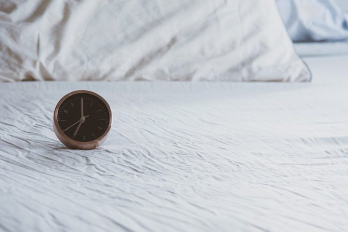 A analog alarm clock on wrinkled bed sheets white color in the morning