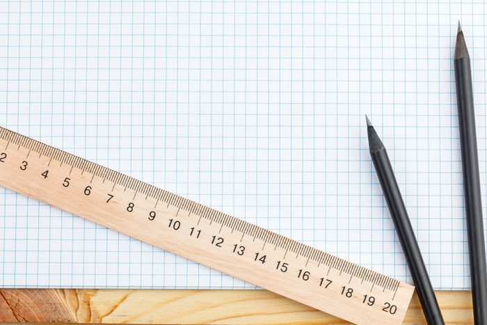 An open notebook and a ruler with two pencils on a wooden background. Office or school supplies, training, planning, office, freelance staff