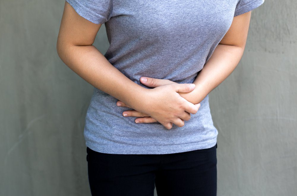 Young woman having a menstruation pain in gray concrete background