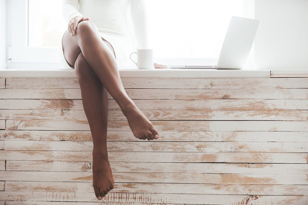 Beautiful seductress. Cropped image of gorgeous young African woman with beautiful legs sitting on the window sill with laptop laying near her
