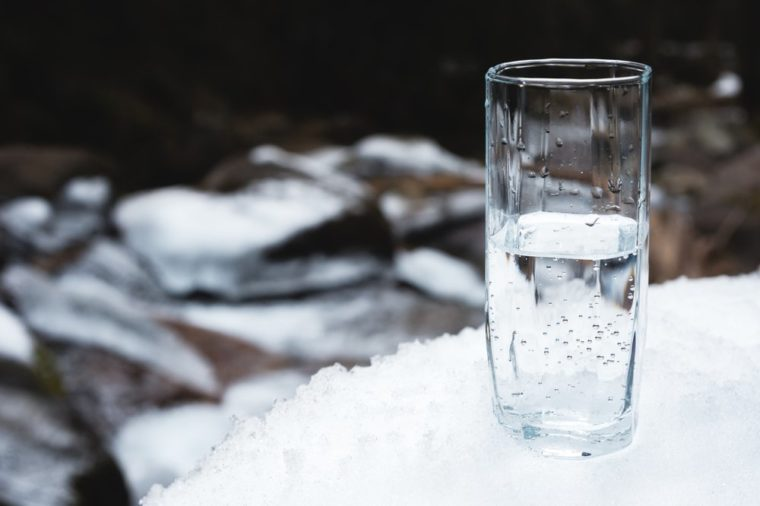 A transparent glass glass with drinking mountain water stands in the snow against a background of a clean mountain river and a forest in winter.