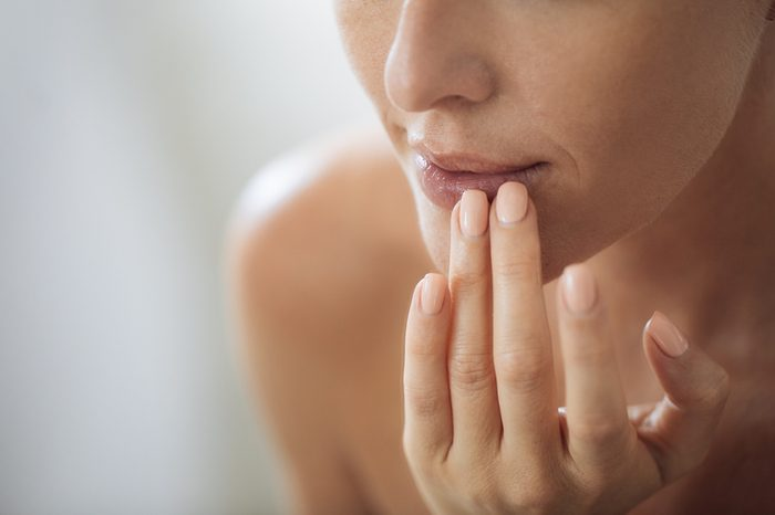 Cropped Caucasian woman putting balm on her lips.