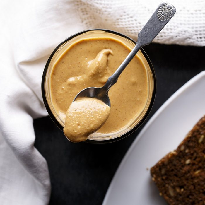 Homemade organic peanut butter, only crushed peanuts inside. Top view.; Shutterstock ID 754716562