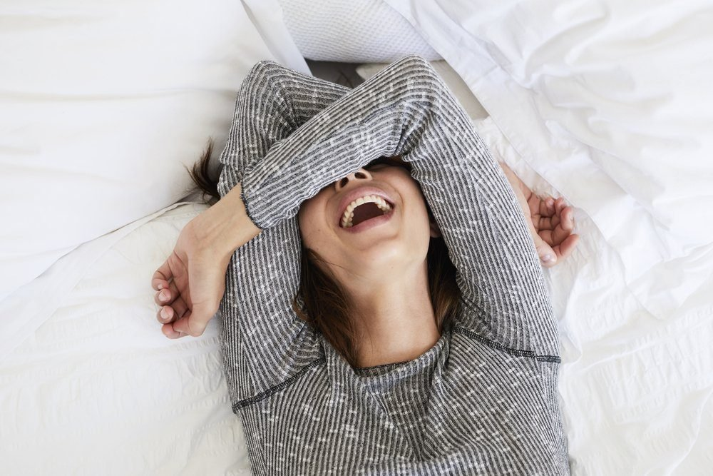 Laughing babe in bed, overhead view