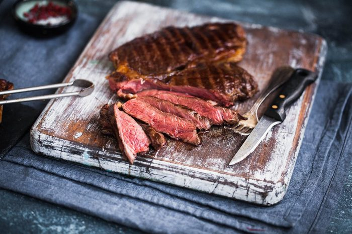 Grilled ribeye beef steak on a cutting board. Hot medium rare beef steak sliced.