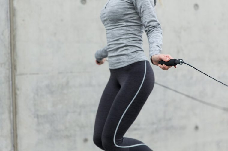 fitness, sport, people, exercising and lifestyle concept - close up of woman skipping with jump rope outdoors