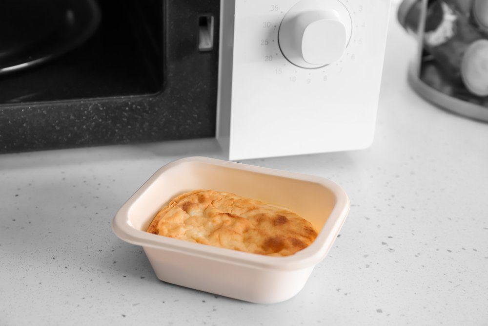 Container of cottage cheese casserole near microwave on table