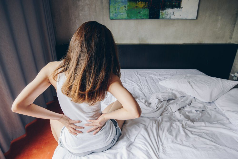 Back view of young woman suffering from Backache or Sore waist after her wake up in the bedroom. Conceptual of woman stretching suffering from sudden back pain.