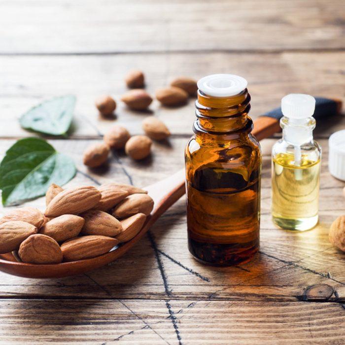 Almond oil in bottle on wooden background.