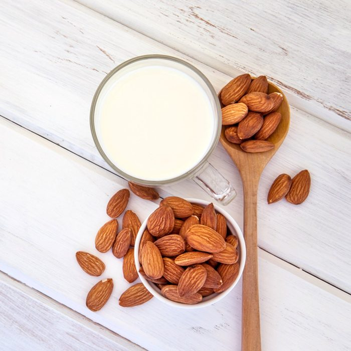 Close up top view of healthy almond milk in drinking glass with seed in white cup and wooden spoon on white wooden table plate